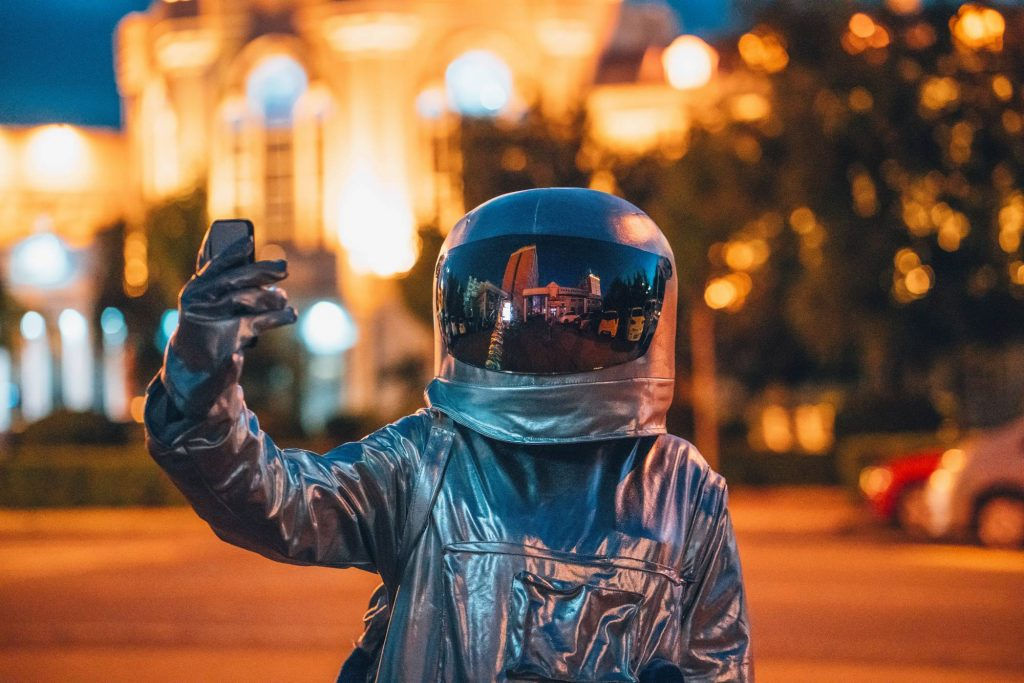 VP 6269648, Spaceman on a street in the city at night holding smartphone. Fotograf: Vasily Pindyurin