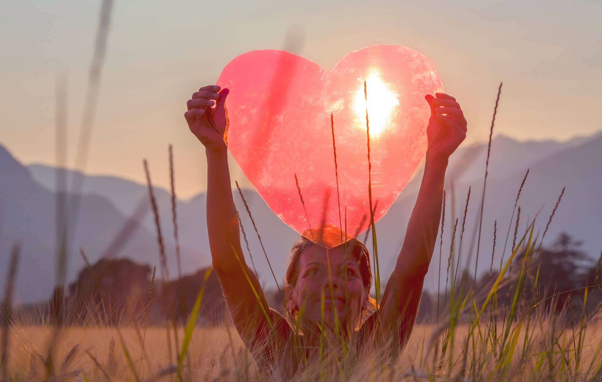 VP 4260316, A Woman Holds Up A Red Heart With The Sun To Shine Through, Locarno, Ticino, Switzerland. Fotograf: Mats Silvan